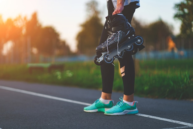 Teenager holds roller skates for inline skating outdoors. Premium Photo