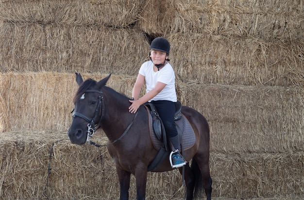 Teenager learning to ride in the riding school Premium Photo