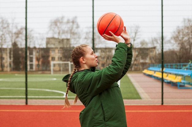 Подросток играет в баскетбол на открытом воздухе Premium Фотографии
