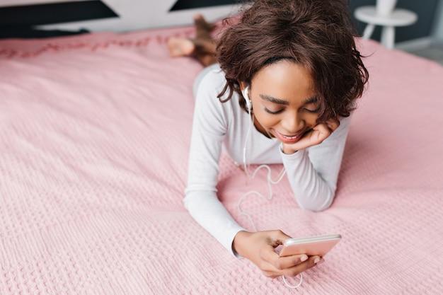 Подросток, симпатичная молодая девушка, лежа на большой розовой кровати, слушает музыку в наушниках, смотрит в смартфон, переписывается с друзьями, отдыхает дома. в красивой футболке с длинными рукавами. вид сверху. Бесплатные Фотографии