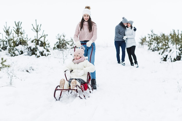 teenager pulling sleigh with sister near parents photo free download