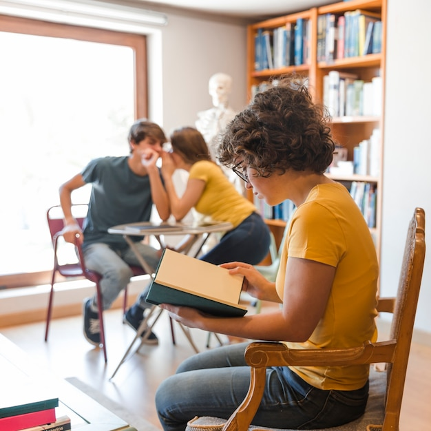 Teenager reading near gossiping classmates Free Photo