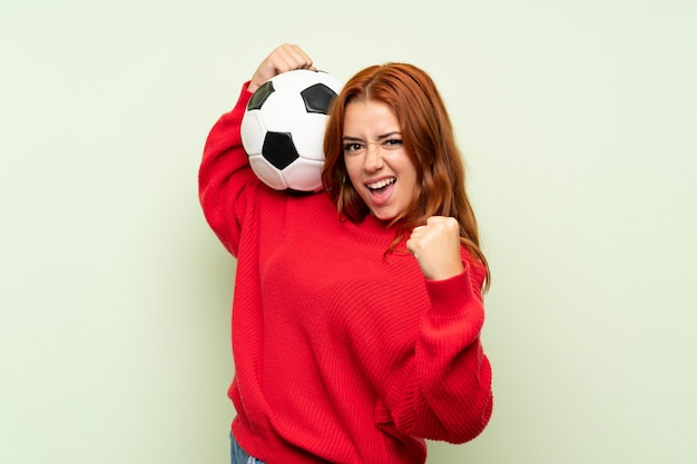 Teenager redhead girl with sweater over isolated green  holding a soccer ball Premium Photo