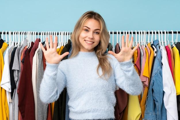 Русская девушка-подросток покупает одежду на синем, считая десять пальцами Premium Фотографии