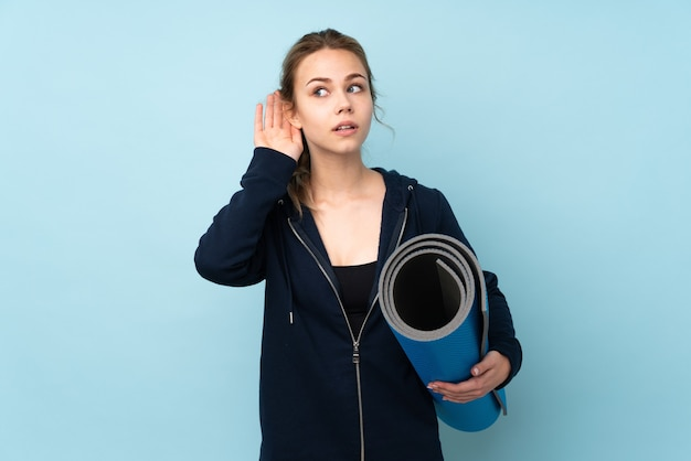耳に手を置くことによって何かを聞いて青い壁に分離されたマットを保持している10代のロシアの女の子 Premium写真