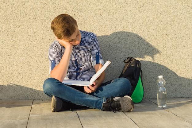 Teenager schoolboy reads textbook Premium Photo