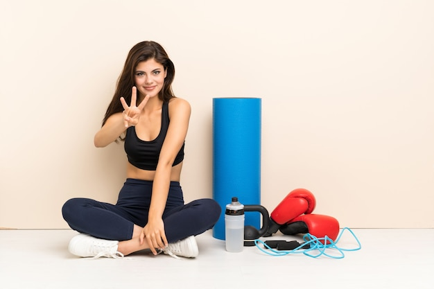 Teenager sport girl sitting on the floor happy and counting three with fingers Premium Photo