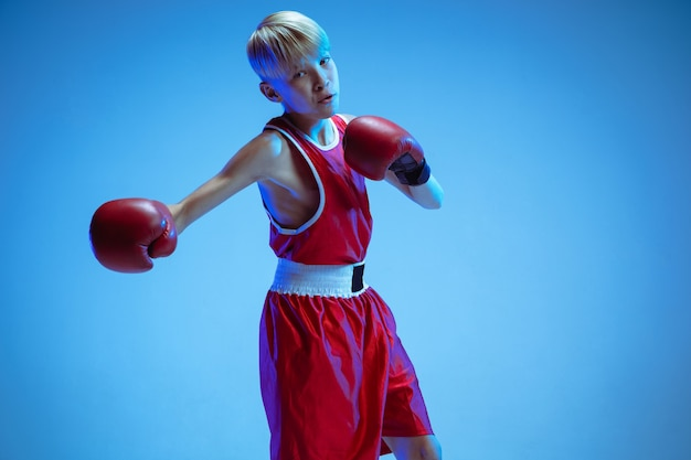 Teenager in sportswear boxing isolated on blue studio background in neon light. novice male caucasian boxer training hard and working out, kicking. sport, healthy lifestyle, movement concept. Free Photo