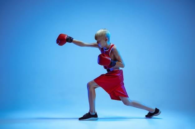 Adolescente nella boxe di abbigliamento sportivo isolato su sfondo blu studio in luce al neon. pugile caucasico maschio novizio che si allena duro e lavora fuori, calci. sport, stile di vita sano, concetto di movimento. Foto Gratuite