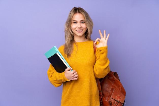 Девушка студента подростка изолированная на фиолетовой стене в представлении дзэн Premium Фотографии