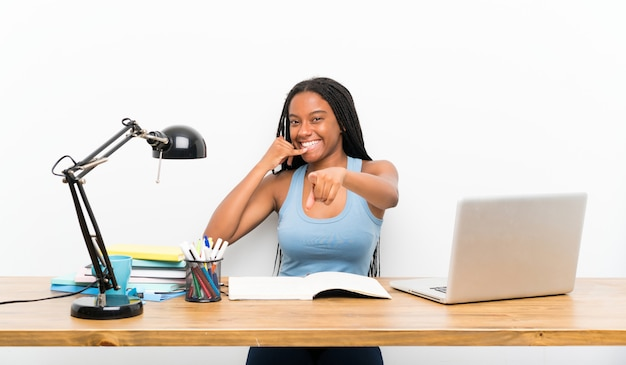 Teenager student girl making phone gesture and pointing front Premium Photo