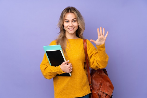 Teenager student girl on purple wall counting five with fingers Premium Photo