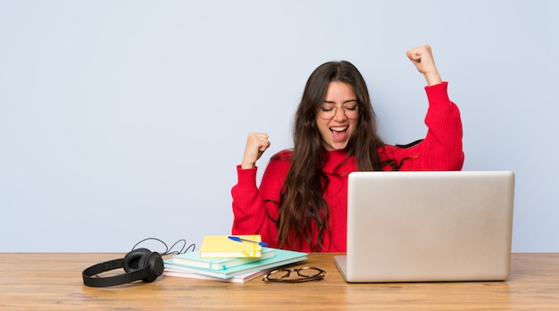 Teenager student girl studying in a table celebrating a victory Premium Photo
