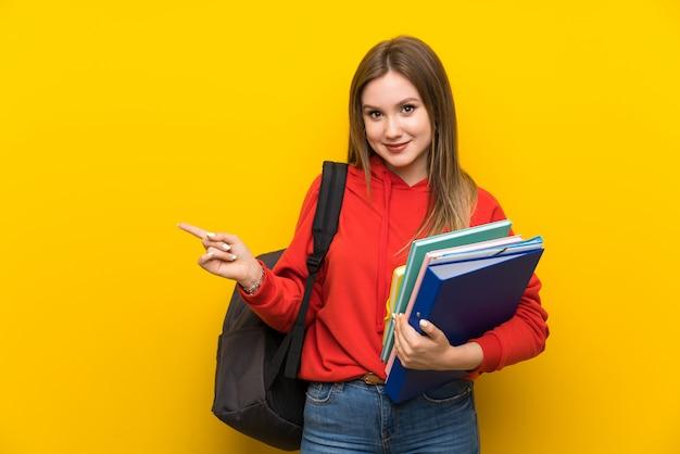 Teenager student girl over yellow Premium Photo