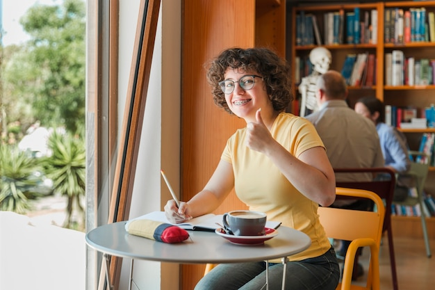 Teenager studying and gesturing thumb-up Free Photo