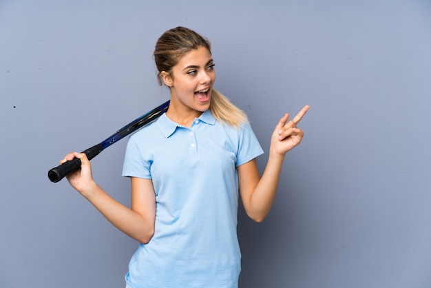 Teenager tennis player girl over grey wall surprised and pointing finger to the side Premium Photo