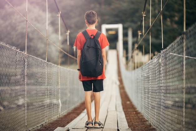 Teenager with a backpack in the mountains, a boy crosses a mountain river on a suspension bridge. Premium Photo