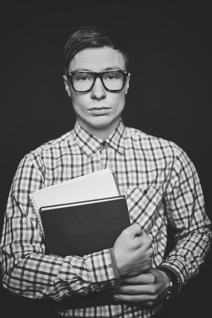 Teenager with glasses holding books Free Photo
