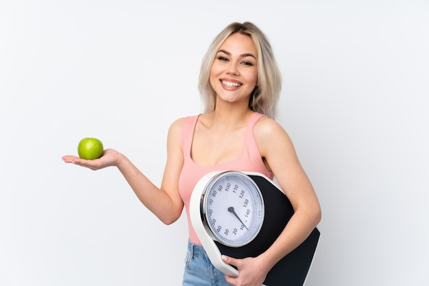 Teenager with weighing machine and with an apple Premium Photo