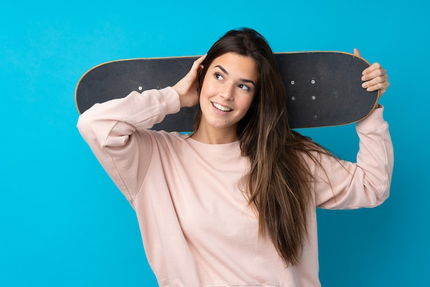 Teenager woman over isolated blue wall with a skate and looking up Premium Photo