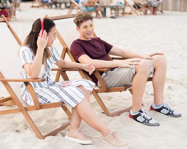 Подростки отдыхают вместе на пляже Бесплатные Фотографии