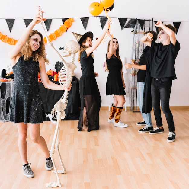 Teenagers in dark clothes smiling and dancing at party Free Photo