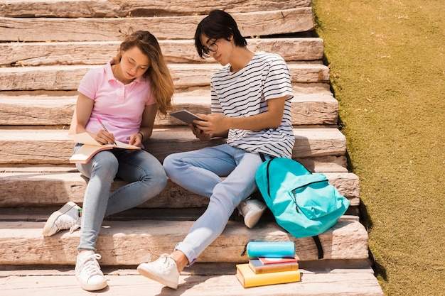 Teenagers doing homework together on stairs Free Photo