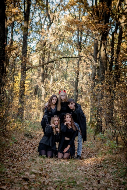 森の中でハロウィーンの衣装を着たティーンエイジャー。 Premium写真
