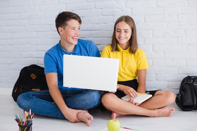 Teenagers laughing and using laptop Free Photo