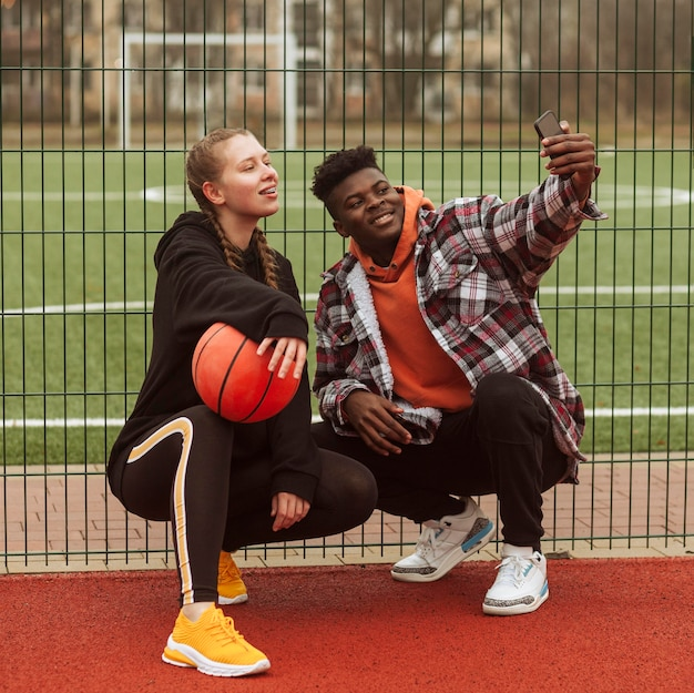 Подростки позируют на баскетбольном поле Premium Фотографии