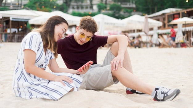 Подростки вместе отдыхают на пляже Бесплатные Фотографии