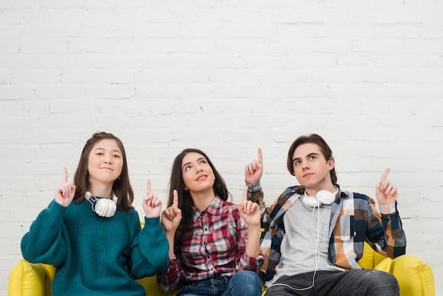 Подростки сидят на диване Premium Фотографии