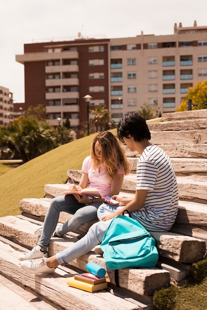 Teenagers studying together on stairs in street Free Photo