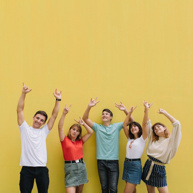Teenagers at summer music festival having good time on a yellow background. Premium Photo