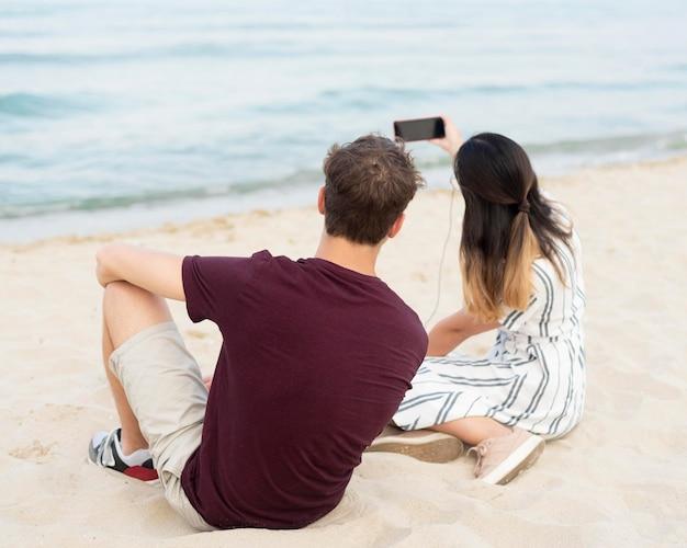 Подростки, делающие селфи вместе на пляже Бесплатные Фотографии