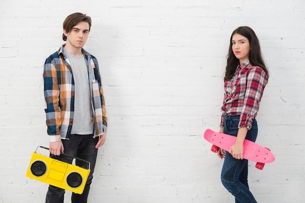 Teenagers with skate and radio Free Photo