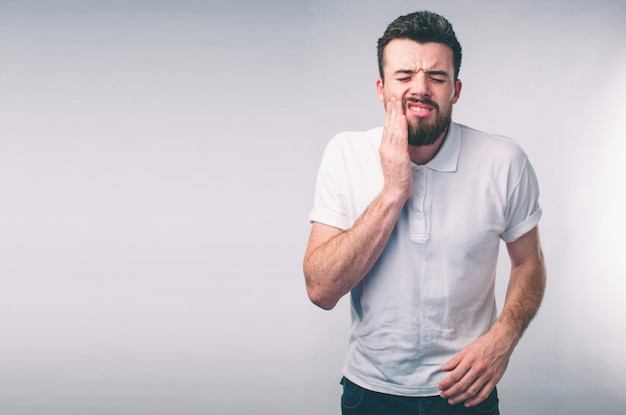 Teeth problem. man feeling tooth pain. closeup of bearded boy suffering from strong tooth pain. attractive male feeling painful toothache. dental health and care concept Premium Photo
