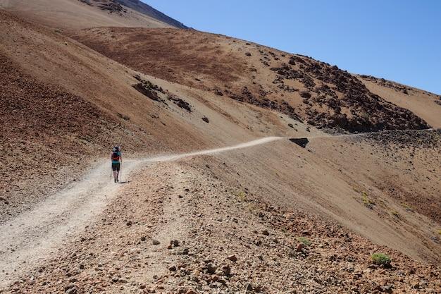 Женщина взбираясь белая горная дорога к teide, тенерифе. Premium Фотографии