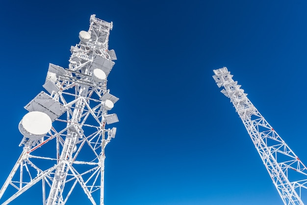 Telecommunication antenna. ice-covered cell tower on the roof of the base radio station located in the highlands. blue sky. Premium Photo