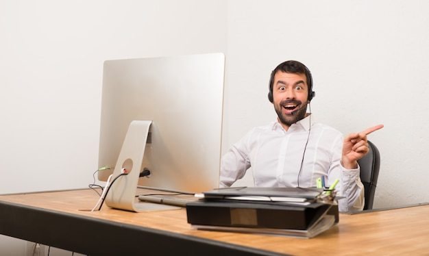 Telemarketer man in a office pointing finger to the side and presenting a product Premium Photo