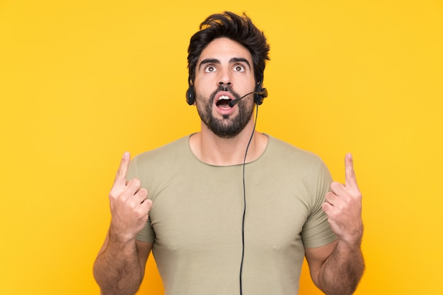 Telemarketer man working with a headset over isolated yellow wall pointing with the index finger a great idea Premium Photo