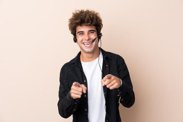 Telemarketer человек, работающий с гарнитурой над изолированной стеной, указывает пальцем на вас Premium Фотографии