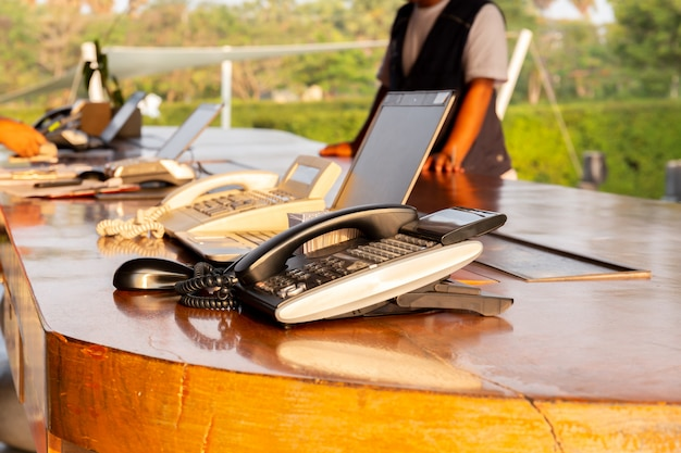 Telephone on hotel reception desk with customer check in at reception counter. Premium Photo