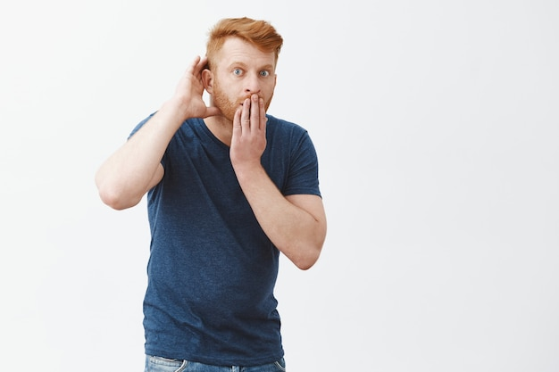 Tell me all details of rumor, listening carefully. shocked impressed handsome redhead guy in blue t-shirt, stooping, covering opened from amazement mouth, holding hand near ear, eavesdropping Free Photo