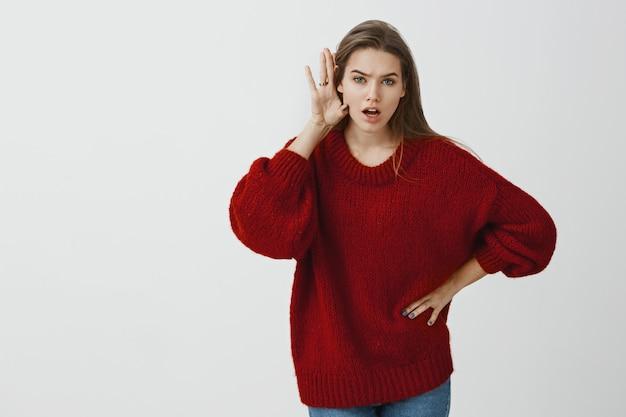 彼があなたに言ったすべてを教えてください。ゆったりとした赤いセーターを着たショックを受けた強烈な魅力的な女性同僚の屋内ショット、カメラに向かって曲がり、耳の近くに手のひらを持ち、噂や噂を広める 無料写真