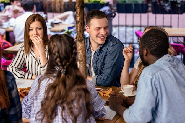 Telling jokes to close friends with informal atmosphere on the open air terrace of a cafe Free Photo