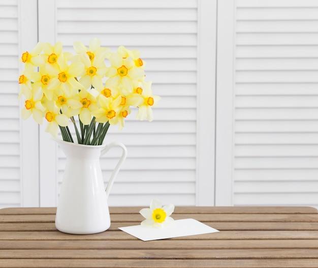 茶色の木製のテーブルの白い招待状カードtempateと白いシャッターに水仙の花の頭 無料写真