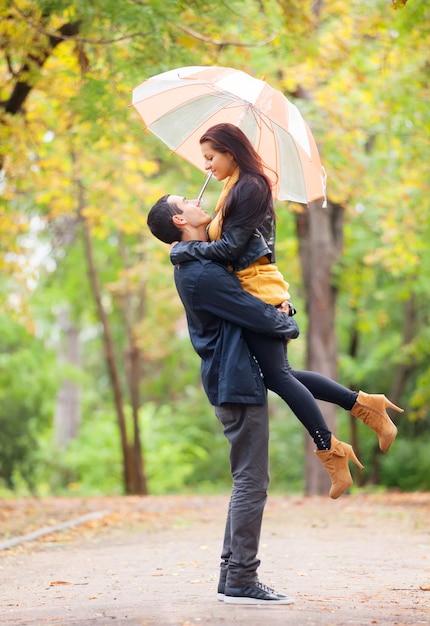 Ten couple with umbrella at the park in autumn time Premium Photo