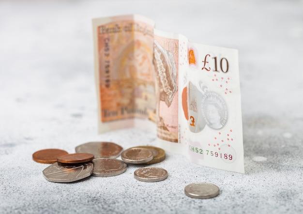 Банкнота в десять фунтов с монетой на светлой поверхности. концепция кризиса мировой экономики. Premium Фотографии