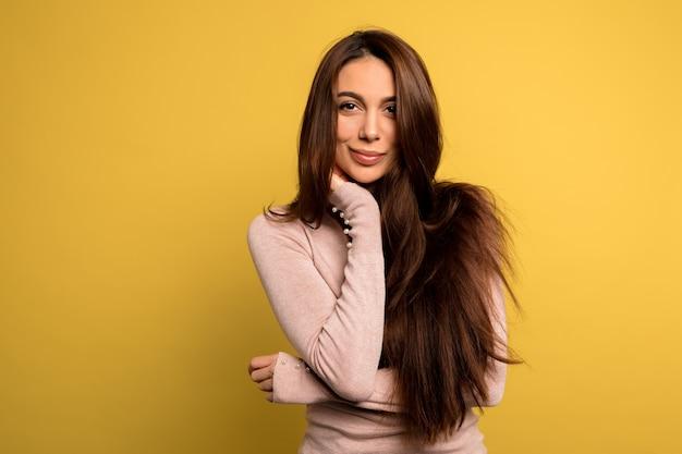 なブルネットの女性のスタジオ撮影をポーズピンクのシャツを着ている黒い髪の美しい優しい美しい少女。 無料写真